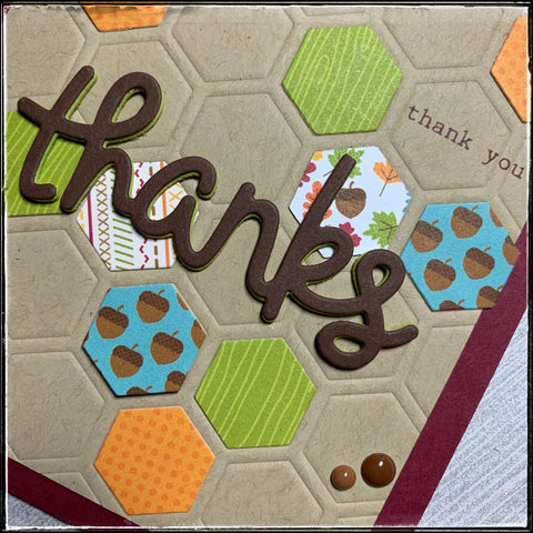 "diagonal up close photo of the details on this card front, including the patterns on the cardstock as well as the layers of the word ""thanks"" and the enamel dots."