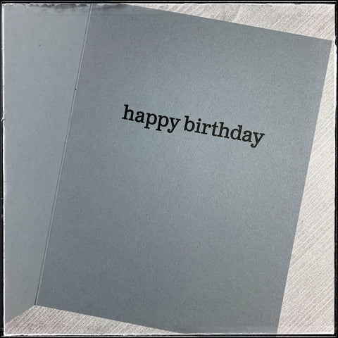 "the inside of this handmade card features the stamped sentiment ""happy birthday"". the sentiment is stamped in black ink and the card base color is grey."