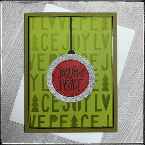 """a multi-layered holiday card with shades of green detailed with red and silver accents. the background has been ink blended through a stencil, revealing the block letters spelling out joy, love and peace. a red circle has been die-cut and features the stamped sentiment """"joy love peace"""" in black ink. the perimeter of the circle has faux stitching. the red circle is layered on a silver circle, also with faux stitching. the red circle is elevated off of the silver circle with foam tape. a thin black vertical line extends from the top of the silver circle to the top of the panel, resembling a hanging ornament. the panel is layered onto a green card base and is bordered by a hand-drawn black glossy line."""