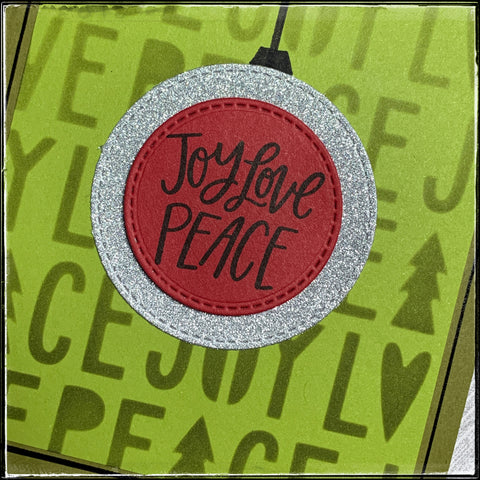 """a detail close up of the ornament created by two layered die-cut circles, both with a faux stitched edge. the top most layer is red and is stamped with the sentiment """"joy love peace"""" to coordinate with the background. a thin black hand-drawn line surrounds the panel and creates a nice border on the green card base."""