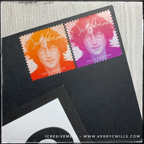 the corner of the black envelope with the usps postage stamps i selected. i chose john lennon stamps merely because they come in a variety of colors and i liked the way that they orange-pink-purple played off of the blending on the front of my handmade card.