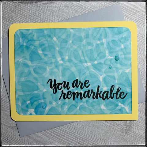 """You are remarkable"" is the main message on this handmade card. A yellow card base sits below a panel that has been stenciled with blue and blue-green inks, creating the background resembling the water in a swimming pool. All of the corners of the panel as well as the card base aside from the lower right have been slightly rounded, which softens the feel of this card. A trio of blue translucent dots surround the sentiment for added dimensional detail. A light grey envelope is included."