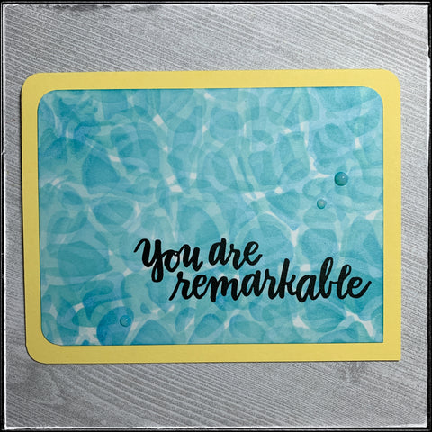 "A flat-lay view of this handmade card which is encouraging as well as complimentary for your recipient. A yellow card base holds a panel which resembles the reflective water inside a swimming pool alongside the stamped sentiment, ""you are remarkable."" A trio of small blue translucent dots provides additional detail around the sentiment. The upper and lower left corners as well as the upper right corner of the card panel and the card base have been rounded to give a softer feel to the card."