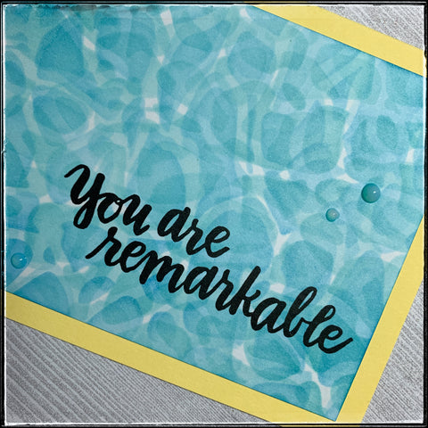 "An angled view of the sentiment, ""you are remarkable"" which has been stamped in crisp black ink. The ink blending on the background really gives the appearance of water in a swimming pool on a summer day. The yellow card base ties into the feeling of the sun. A trio of small blue translucent dots accent the sentiment, along with three rounded corners on both the card panel as well as the card base."
