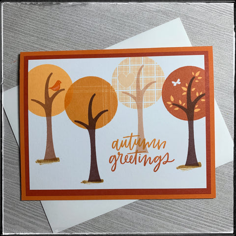 """A fall-themed greeting is the main sentiment on this handmade card! """"Autumn greetings"""" is stamped in an ombre color scheme with orange fading from light to dark alongside four trees. Each tree top is a circle in a shade of orange as the concept of this card is a monochromatic color scheme. Each tree top is slightly different, both in pattern and in color. They are staggered across the white card panel which is layered on a darker orange panel which is layered on the classic orange card base. A white envelope is included."""