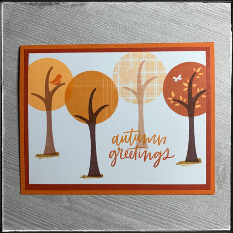 """The flat-lay view of this seasonal handmade card. """"Autumn greetings"""" is stamped in shades of orange and overlaps the trunk of one of the four trees that are stamped across the front panel. Each tree top is a slightly different shade of orange, creating a mostly monochromatic look on this handmade card."""