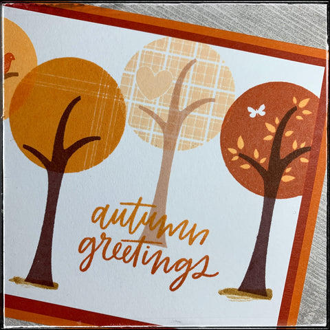 """An up close detailed view of several of the stamped trees and the details on the tree tops. Thin striped lines are crisp and clear in a medium shade of orange. The lightest colored tree top is a beautiful plaid pattern with an inlaid heart design. The third tree top shown is the darkest color orange and features some lighter orange colored leaves. The sentiment """"autumn greetings"""" overlaps the trunk of the middle tree in two shades of orange ink which are blended in an ombre color scheme."""