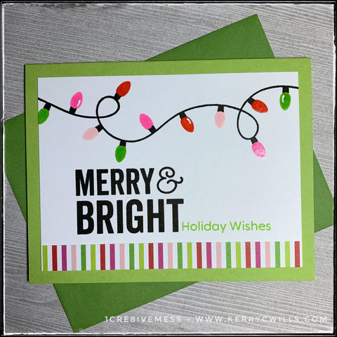 "This handmade holiday card screams merry & bright - right in the sentiment that's stamped on the white card panel! The complete sentiment reads ""merry & bright holiday wishes"" in a combination of black and green inks. A strand of brightly colored holiday lights twists and turns along the top portion of the card and the colors of the festive bulbs coordinate with the vertical striped patterned paper near the bottom of the card front. A leaf green colored envelope is included."