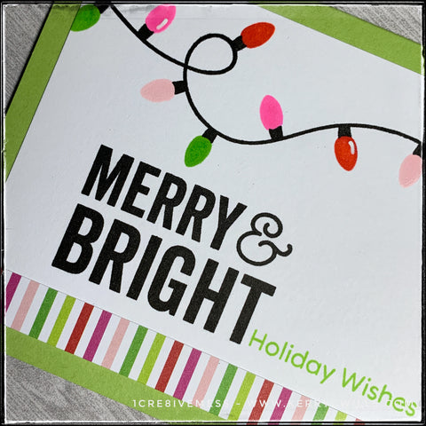 An angled flat-lay view of the sentiment and patterned strip on this handmade holiday card. Colorful bulbs decorate the top portion of this card as if strung along across the top. The colors of the lights coordinate with the vertical striped patterned paper that accents the bottom part of the panel. A bright green card base is blank inside with plenty of room for the message to your recipient.