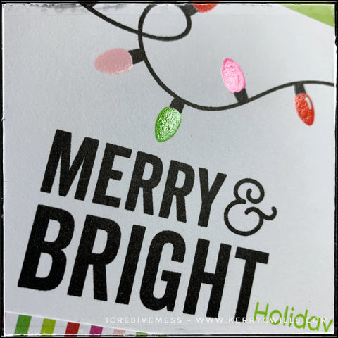 "An angled view of the holiday bulbs where the reflective quality is visible. The bulbs shine and glisten as the light hits them. It's a nice detail against a matte background. The sentiment ""merry & bright"" is stamped in black ink and the secondary sentiment, ""holiday wishes"" is stamped in green ink."