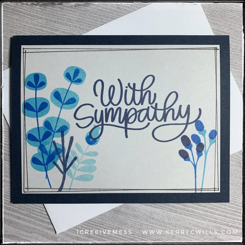 """Handmade card 28/100-2 from #the100dayproject, this sympathy card has a big bold sentiment in dark blue ink that matches the color of the card base. The sentiment is written in a scripty, cursive font and reads """"with sympathy"""". Surrounding the sentiment are small bunches of various wildflowers, all stamped in shades of blue. Light blue leaves and dark blue buds might be unconventional, but they fill the space so nicely and the color scheme is somewhat calming. A bright white envelope is included and is shown with the card."""