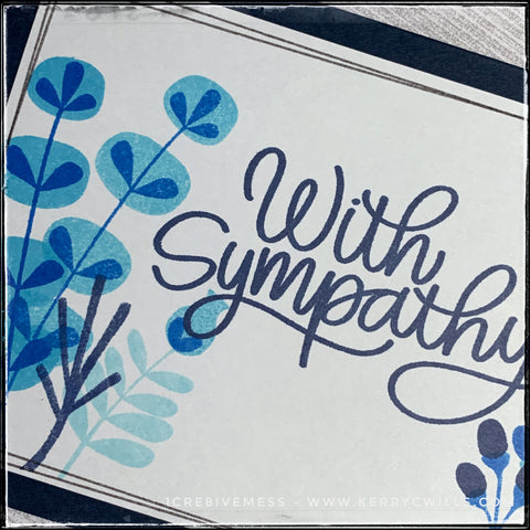 A flat-lay angled view of some of the details on the front of this handmade sympathy card. Clusters of flowers in a variety of styles emerge from the left and right sides of the card panel. They are stamped in shades of blue ink to coordinate with the card base. Hand drawn thin grey lines surround the perimeter of the grey panel and overlap the floral design.