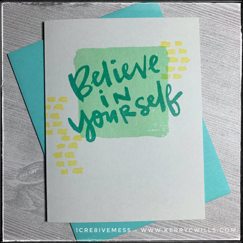 """An encouraging handmade card - this features a bold sentiment that reads """"believe in yourself"""" in aqua text overlapping a lighter green square. Small, yellow dash marks accent the square on either side. The card is made from a light grey card base and comes with an aqua envelope."""