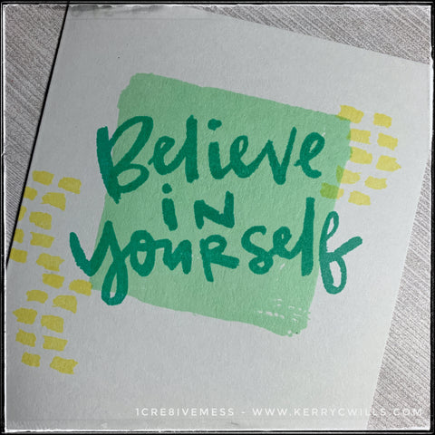 """An angled flat-lay of the card front where the sentiment is front and center. Stamped in aqua ink overlapping a lighter green square is the sentiment """"Believe in yourself."""" Small clusters of yellow dashes are framing in the sentiment on either side of the square which isn't perfectly square. It's designed to look like a paintbrush swiped paint on the card base and the result is fantastic."""