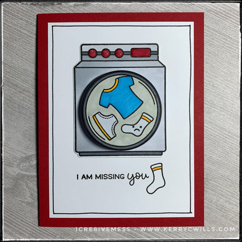 "A flat-lay view of this handmade card designed to be sent to a friend or loved one that's being missed. A washing machine that has been stamped and die-cut is the center focal point. The middle drum is elevated off of the card base and wiggles back and forth. The sentiment ""I am missing you"" is stamped next to a lonely little sock. Hand drawn lines surround the perimeter of the white card front on top of the red card base."