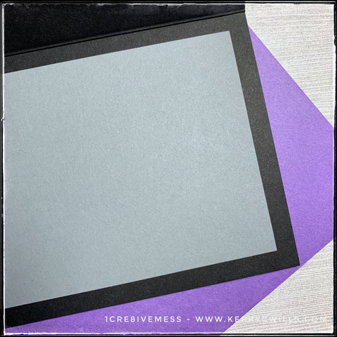 An angled view of the inside of this slimline handmade card. A black card base holds a smaller, grey panel on the inside of the card. This helps to ensure your message to your recipient will be easy to see and easy to read. A thin border surrounds the grey panel so that the black card base is visible when the card is open. Also visible is the purple envelope that's included as well.