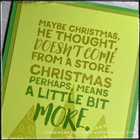 """An angled flat-lay of the card front, the detail in the sentiment is clear. The sentiment has been stamped in an ombre fade with various shades of green, overlaying a trio of triangle trees. The sentiment reads """"Maybe Christmas he thought, doesn't come from a store. Christmas perhaps, means a little bit more."""" and is from the famous movie [and book] """"The Grinch."""""""