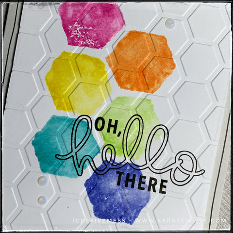 """An up-close, detailed flat-lay view of the designs and texture on the handmade card front. There are six hexagons with a very relaxed feel to them stamped in a rainbow of colors including pink, orange, yellow, light green, aqua and blue. The sentiment """"oh, hello there"""" overlaps the hexagons and is stamped in black ink. The entire card front panel has been dry embossed with an all-over pattern of hexagons, complete with a deep texture. Three small clear dots add some additional dimension."""