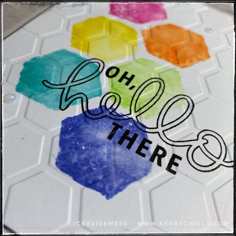 """A horizontal angled flat-lay view of the texture and dimension on this handmade card. The colored hexagons sprawl across the card front in rainbow order and are overlapped by both the stamped sentiment """"oh, hello there"""" as well as the all over texture of the repeating hexagon pattern."""