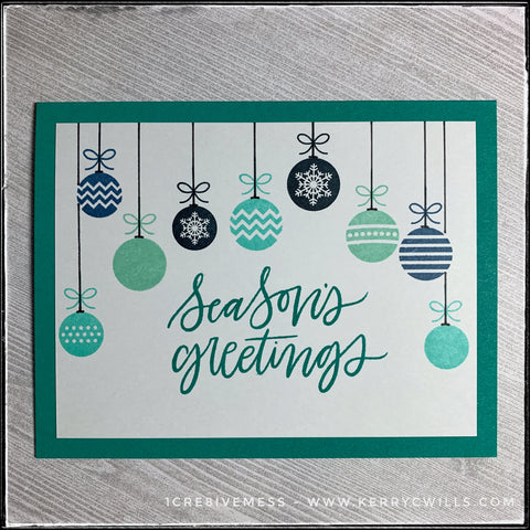 """A classic flat-lay of this handmade holiday card, the sentiment """"season's greetings"""" is stamped in the center of the card front. The color coordinates with the color of the card base. A series of nine hanging ornaments graces the top portion of the card, cascading along the top. Shades of aquas, turquoises and deep blues evoke a wintery feeling."""