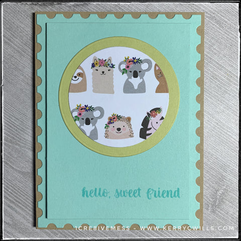 """A flat-lay view of this handmade friendship card. Decorative patterned paper with a slew of wildlife animals wearing flowery headdresses adorns a die-cut circle near the top center of the card panel. Designed to resemble a postage stamp, the edges of the panel have a scalloped detail and the center portion of the panel is elevated off of the card base for added dimension. The stamped sentiment reads """"hello, sweet friend"""" and is stamped in aqua ink near the bottom right corner of the card."""