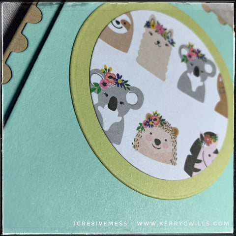 An angled view of the dimension of the inner postage stamp panel that's been elevated with foam tape. Details of the patterned paper featuring the smiling animals wearing flowered headdresses is also visible.