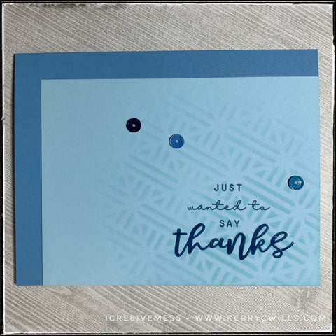 """A flat-lay image of day 41's handmade card, complete with a monochromatic color scheme and thank you theme. A stenciled background emerges from the bottom right side of the card in blue ink and is layered under the sentiment, """"just wanted to say thanks"""" which is stamped in blue ink. A smattering of three sequins adds detail to the card front."""