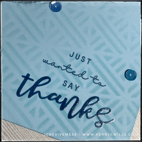 """An angled view of the detail on this handmade card front - including the sentiment """"just wanted to say thanks"""" which is stamped in blue ink. The word """"thanks"""" has been layered with a clear gel glaze pen, adding a glorious shine and reflection to the word. Several small sequins can be seen overlapping the stenciled monochromatic background."""
