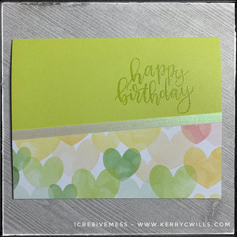 A flat-lay of the happy birthday card in this all occasion handmade card set. A lime green card base coordinates with the colors of hearts on the patterned paper section of the card and is accented by a narrow strip of iridescent vellum.