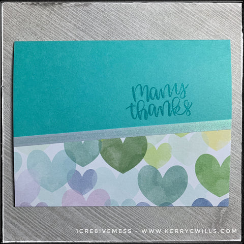 A flat-lay of the many thanks card in this all occasion handmade card set. An aqua card base coordinates with the colors of hearts on the patterned paper section of the card and is accented by a narrow strip of iridescent vellum.