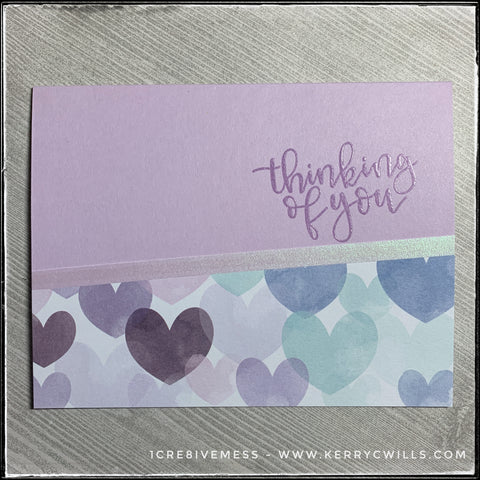 A flat-lay of the thinking of you card in this all occasion handmade card set. A light purple card base coordinates with the colors of hearts on the patterned paper section of the card and is accented by a narrow strip of iridescent vellum.