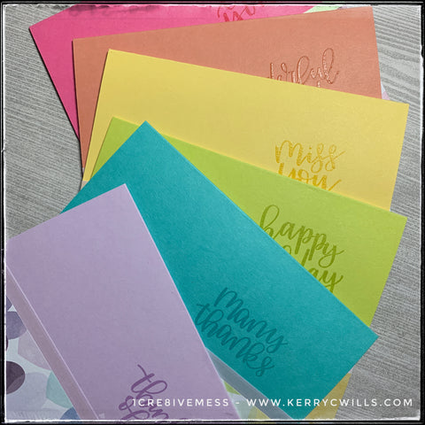 A flat-lay display of the rainbow of six handmade all occasion cards. Each card features a strip of decorative patterned paper in a rainbow heart pattern, as well as a strip of iridescent vellum and heat embossed sentiment. These are great individually as well as in the set.