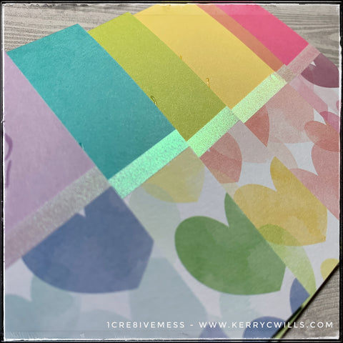 An angled view of the rainbow of all occasion handmade cards, the sliver of iridescent vellum shimmers and shines along the edge of patterned heart paper. Each card base is a different color, coordinating with the color of the hearts on the card front.