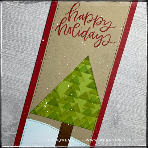 """This angled flat-lay view includes the sentiment """"happy holidays"""" in red ink, in a scripty font. The red color coordinates with the color of the slimline card base. The faux-stitched detail is visible around the edges of the card panel, the tree, tree trunk and snowbank. Inked patterns add dimension and detail."""