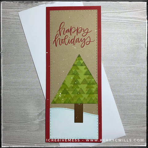 """A vertical style slimline card, the stamped sentiment on this reads """"happy holidays"""" in red ink in a scripty font near the top of the card. Faux stitched detail is evident all around the edges of this front card panel, as well as on the details. There's a die-cut triangle which creates a tree and has been stenciled with a repeating pattern of triangles in shades of green. A snowdrift grounds the tree near the bottom of the card. White flecks of paint are scattered across the card front to look like snow."""