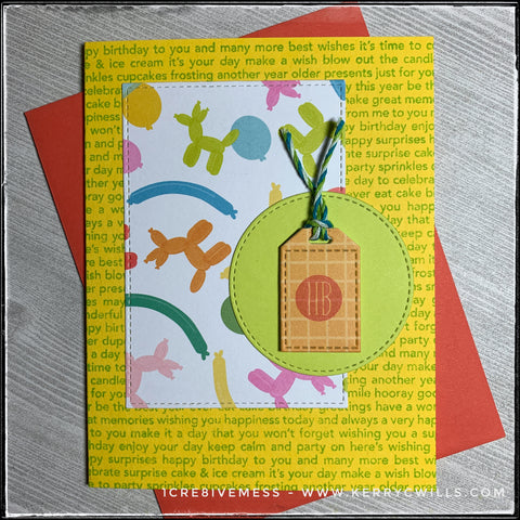 """Paired with a coral-red envelope, this handmade birthday card features a text filled background, complete with all sorts of birthday-related sentiments. The text is green on a bright yellow background. A rectangle with a faux stitched border features a pattern full of colorful balloons and balloon animals. Overlapping the rectangle is a green die-cut circle, also with faux stitched detail around the perimeter. Layered with foam tape on top of the circle is a small tag which has an orange grid pattern and has been stamped with a small circular design with """"hb"""" in red ink. Green, blue and white baker's twine is tied at the top of the tag."""