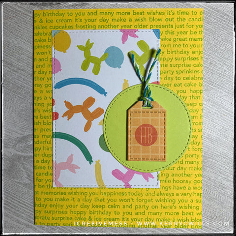 """This handmade birthday card features a text filled background, complete with all sorts of birthday-related sentiments. The text is green on a bright yellow background. A rectangle with a faux stitched border features a pattern full of colorful balloons and balloon animals. Overlapping the rectangle is a green die-cut circle, also with faux stitched detail around the perimeter. Layered with foam tape on top of the circle is a small tag which has an orange grid pattern and has been stamped with a small circular design with """"hb"""" in red ink. Green, blue and white baker's twine is tied at the top of the tag."""