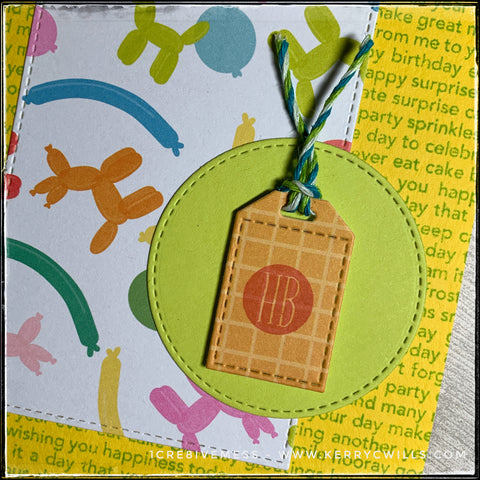 """A detailed close up of the small die-cut tag layered with foam tape over a bright green die-cut circle. The tag features an orange grid pattern and has been stamped with a small red circle, revealing the letters """"hb"""". Green, blue and white baker's twine is loosely tied to the top of the tag. In the background, text celebrating birthdays can be seen stamped in green ink over a yellow background which is the card base."""
