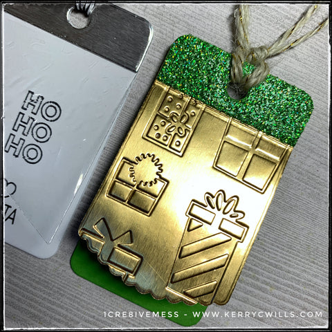 The most successful tag of the three, a green card base lies beneath a gold foil top layer with an embossed texture and pattern full of presents. The top portion of the tag that's been reinforced with an additional layer of cardstock is a glittery green color. There's natural twine with gold accents extending from the tag for adhering to your gift.