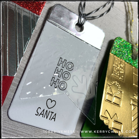 "Details of one of the three tags - stamped on a white tag base are the words ""Ho Ho Ho"" stamped vertically with a small heart and the word ""Santa"" underneath. The top layer has been cut from clear acetate and is embossed with a snowflake texture. The pattern is a little hard to see, so this wasn't the most successful tag I've ever made."