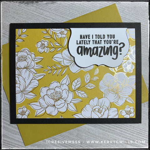 "This handmade card has a complimentary sentiment and features a regal color scheme, complete with gold accents. A black card base holds a panel of decorative patterned paper in a floral pattern with gold accents. A small white scalloped die-cut is elevated off of the card base and houses the sentiment ""Have I told you lately that you're amazing?"" which is stamped in black ink. The color of the card panel is a combination of citrine and topaz and has a true jewel tone to it. A similar colored envelope is also shown and is included with this card."