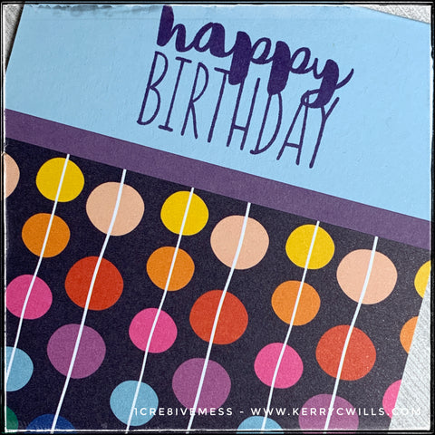 "A diagonal view of the details on this handmade birthday card, the colorful polka dots can be seen cascading in vertical rows, connected by a thin white line. The light blue background allows the sentiment ""happy birthday"" stand out, especially with the dark blue color it's been stamped in. The colors are bright and cheerful, ideal for a festive, celebratory birthday card!"
