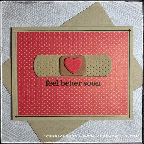 """A handmade card designed to help you feel better from any kind of ailment or illness. A kraft card base coordinates with the included envelope and sits below a patterned panel with tone on tone red polka dots. Centered on the card front panel is a bandaid that's been die-cut from fun foam! Three layers are stacked high - the base, the middle portion where the sterile pad is located, and then a tiny heart layered on top. Beneath the die-cut bandaid is the stamped sentiment, """"feel better soon"""" in black ink. A thin black line surrounds the perimeter of the patterned panel on the card base."""