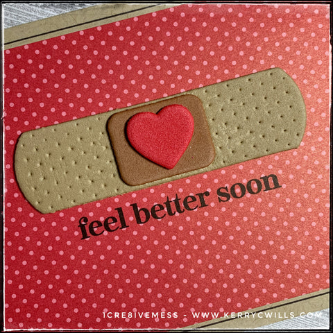 """An up-close, angled view of the details on this handmade card front. The image of a bandaid has been die-cut from fun foam with three separate layers. The sentiment stamped below the bandaid reads """"feel better soon"""" in black ink. The decorative dots on the sides of the bandaid coordinate with the dots on the background patterned paper which is red with tone-on-tone dots."""