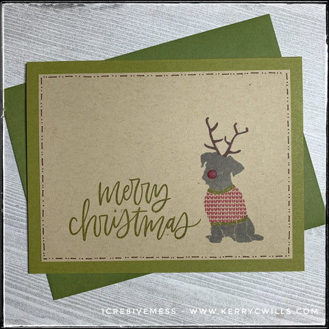 "A seasonal handmade card, the sentiment featured reads ""merry christmas"" in a handwritten scripty font. The sentiment is stamped in green ink on a kraft panel, which is mounted on a green card base - coordinating with the ink color. Near the right side of the card is the image/silhouette of a doggo, wearing antlers and a holiday sweater. His nose is a 3D raised translucent red dot for added holiday spirit. Hand drawn lines and dots surround the perimeter of the kraft panel in a dark brown shade. A mossy green envelope is included."