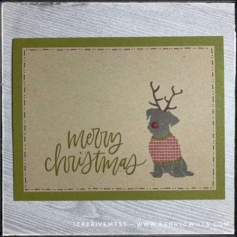 """Merry Christmas"" is stamped in a mossy green ink near the bottom left corner of this handmade holiday card. Next to it on the right is the image of a doggo, wearing a festive holiday sweater as well as a pair of antlers. His nose is a 3D dot, slightly translucent and red to play off of Rudolph! Hand-drawn lines and dashes in brown ink surround the perimeter of the kraft card panel that's layered on a mossy green card base. Anyone who loves doggos is sure to appreciate this card!"