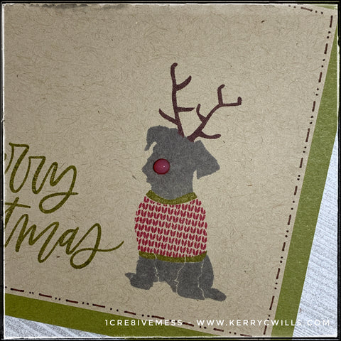 An angled, up-close view of the details of the stamped dog on the front of this holiday card. A sitting dog is wearing a red and green sweater along with festive antlers and a bright shiny nose. Hand drawn lines and dots box in the kraft panel on the green card base.