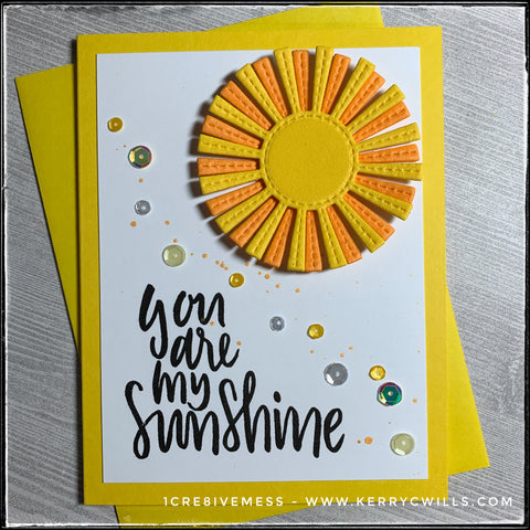 """This bright and energetic handmade card is sure to make your recipient smile with the happy yellow tones and upbeat sentiment. """"You are my sunshine"""" is stamped in black ink near the bottom left of the white panel, which is layered on a bright yellow card base. Two layers of fun foam in yellow and orange are stacked together creating a radiating sunshine with faux-stitched detail. The sunshine is elevated off of the card base, creating the 3D element on this card. A smattering of sequins in shades of yellow and clear dance across the card front and are accented by random yellow flicks of shimmery paint."""