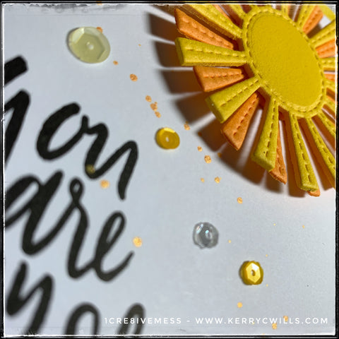 """An angled view of the shiny, sparkly sequins smattered across the card front panel. Various shades of yellow are seen next to the sentiment, """"You are my sunshine"""" which is stamped in black ink. Near the top right of the photo is a glimpse at the 3D sunshine, die-cut from layers of fun foam."""