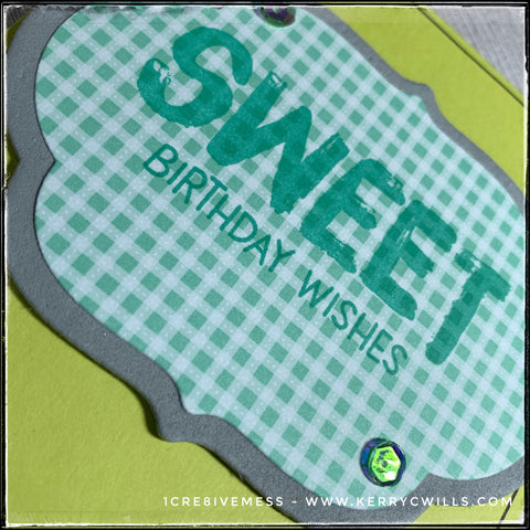 "An angled flat-lay of the card front where the dimension of the die-cut label is visible. Two layers are combined: the bottom grey layer is cut from foam and the top patterned layer is heavy cardstock. The sentiment ""Sweet birthday wishes"" is stamped in aqua ink and accented by a small smattering of shiny reflective sequins."